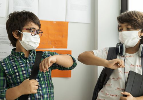 young boys elbow bumping in school while wearing masks