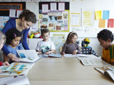 Teacher looking at books with young children