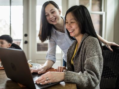 Mother and daughter smiling at the computer