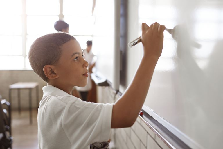 boy writing on board in classroom