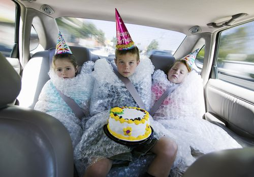 3 kids in the backseat of a car wrapped in bubble wrap