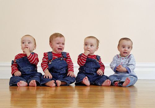 Quadruplets in overalls sitting in a row