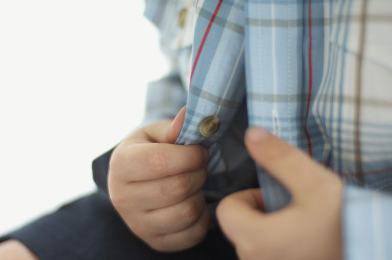 Boy's hands on open, checked shirt, close-up