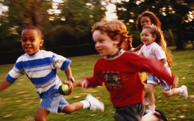 Children (3-8) running in park (blurred motion).