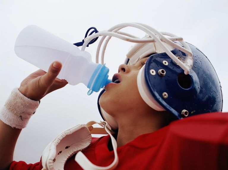 Boy (10-12) in football uniform drinking from water bottle, close up