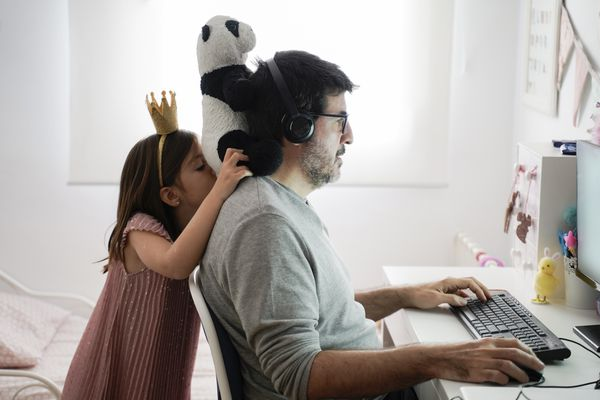 Parent working from home with child behind them