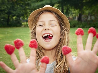 Girl with raspberries on fingers, close up