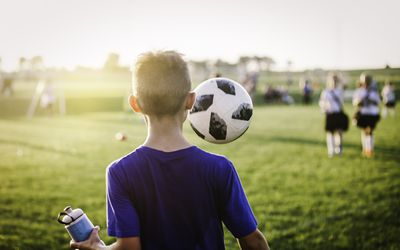 11 year old boy juggling soccer ball while walking off soccer field