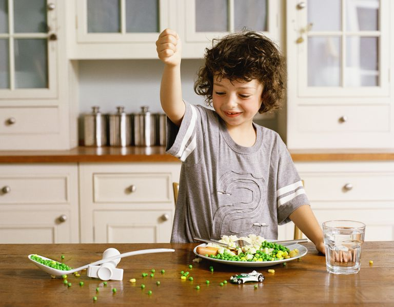 Young boy playing with his food at the dinner table