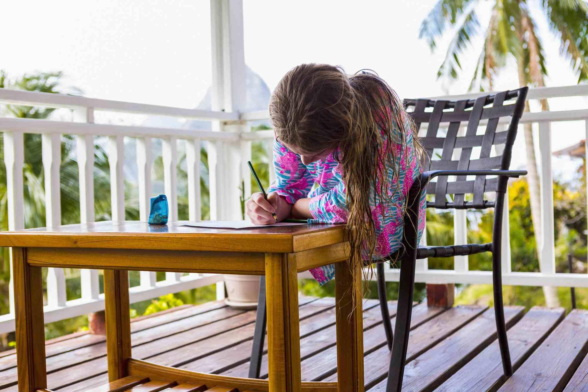 Girl doing homework on porch