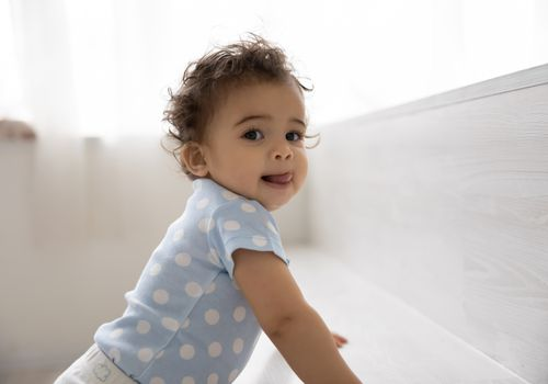 Portrait of cute small African American baby toddler child have fun on comfortable bed at home. Little biracial infant child kid play indoors, wear organic cotton natural clothes. Childcare concept.
