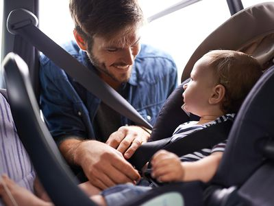 Father putting baby in car seat
