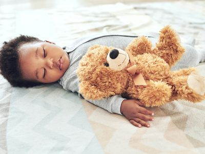 Baby wearing onesie sleeping on bed with teddy bear