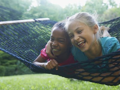 Two best friends laughing on a hammock