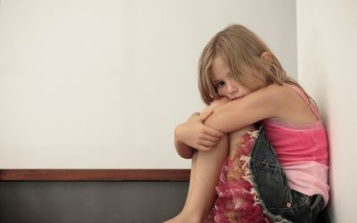 natural and logical consequences - sad girl sitting and hugging herself