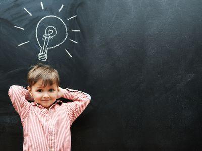 boy with lightbulb above his head on chalk board