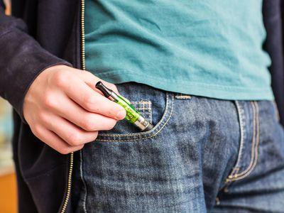teen pulling vaper out of pocket