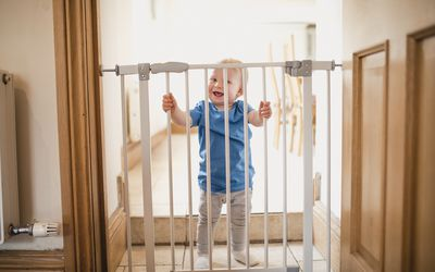 Small Boy Holds On To Safety Gate