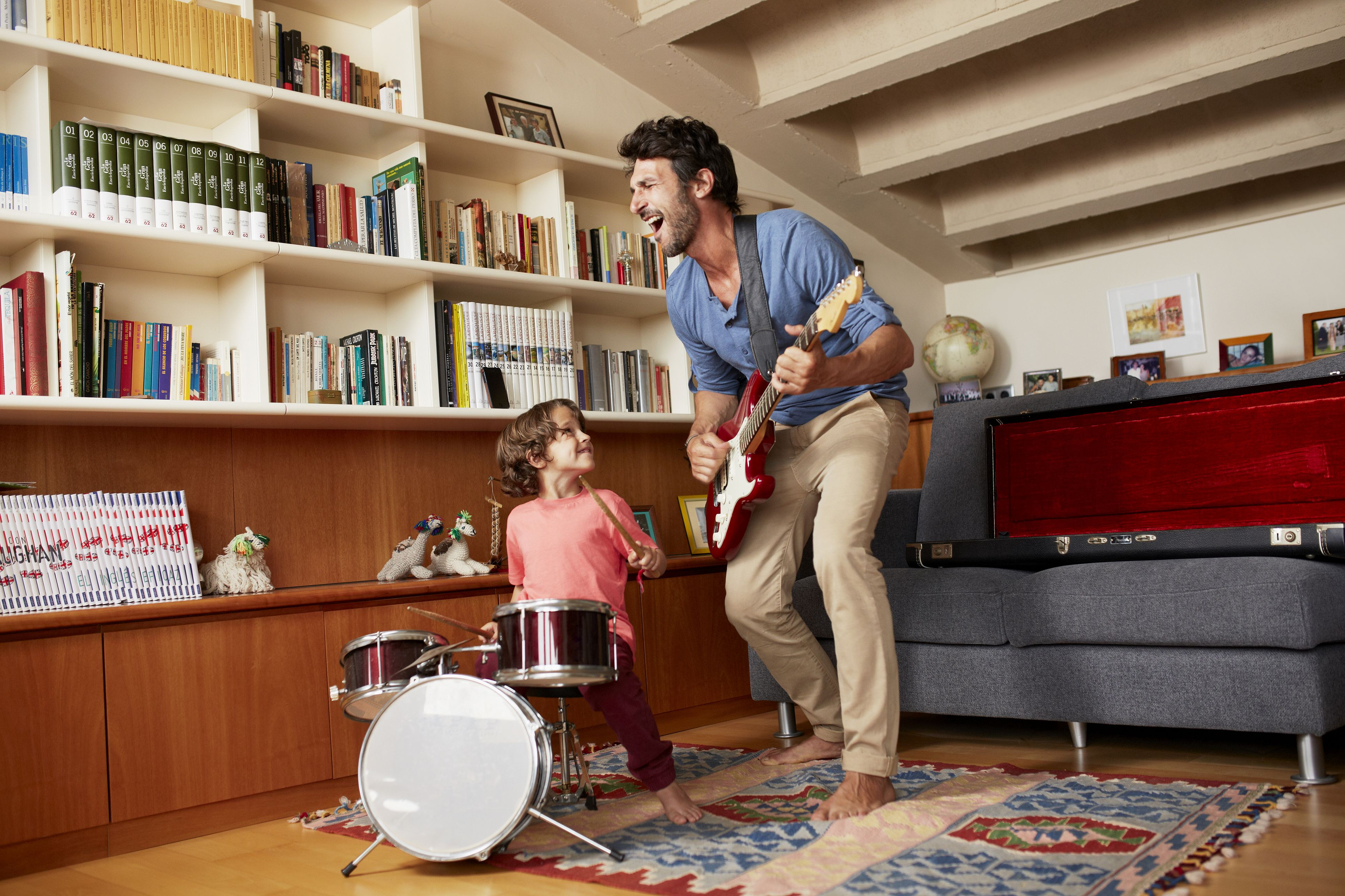 Father and son playing musical instruments in a living room