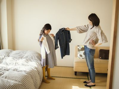 Mother and daughter picking out clothes in bedroom