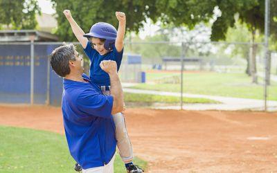 Good sports parent - dad and son celebrating at baseball game