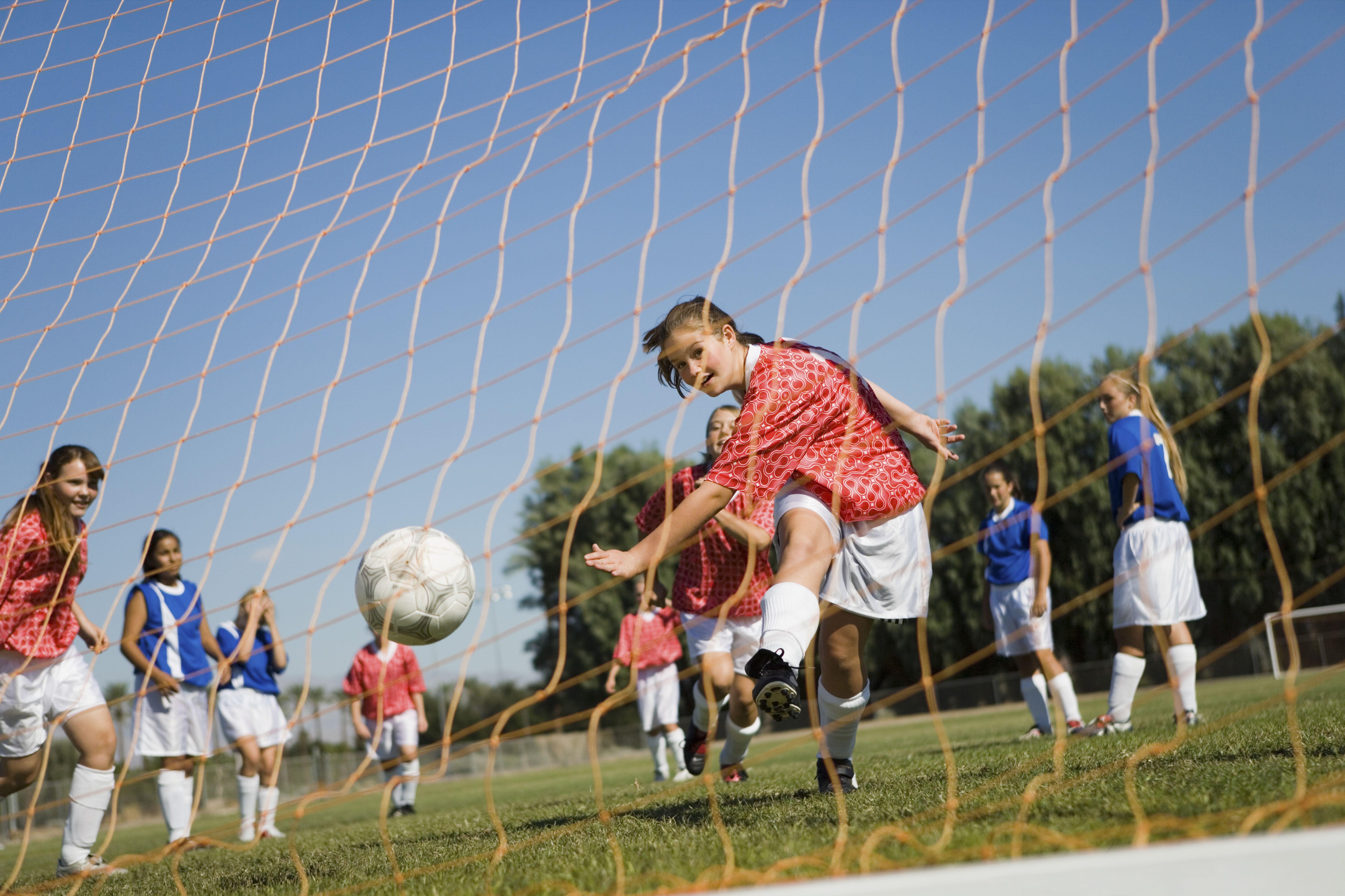 Teenage girl kicking a soccer goal