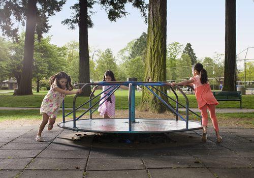 3 girls pushing carousel in playground