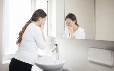a pregnant woman by a bathroom sink with her hand over her mouth, looking nauseous