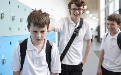 A boy being bullied by classmates in a school hallway