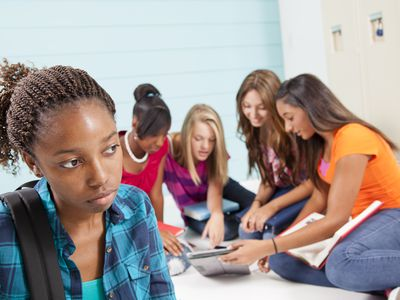 Girl standing away from a group of teens.
