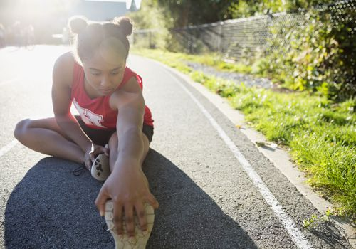 Teen fitness - High school track athlete stretching