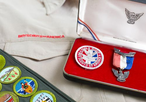 Boy Scout eagle pin and patch with uniform and merit badges
