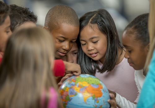 Group of young students looking at a globe.