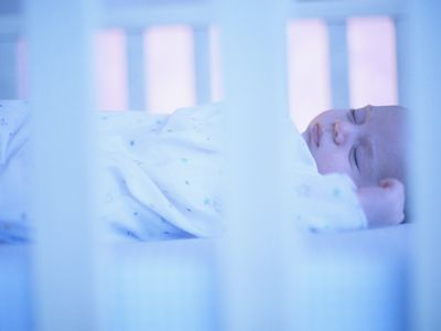 Baby in crib sleeping on back