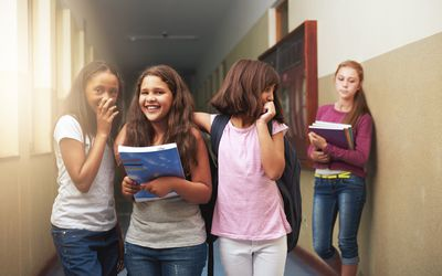 group of girls talking and laughing about other girl