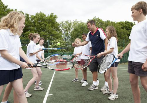 Group of kids with tennis rackets and a coach