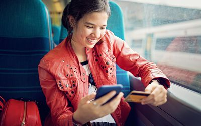 Young teenage girl is shopping online/making reservation in the train