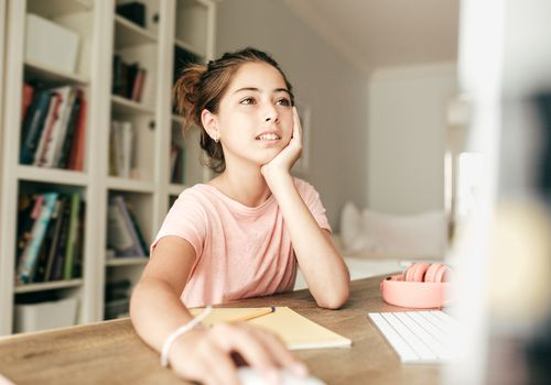 Teenage girl in a pink shirt sitting at a computer