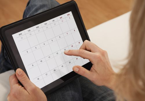 Close-up of woman using calendar on digital tablet