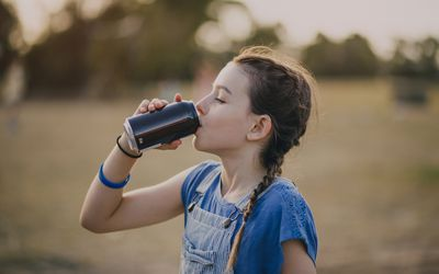 Tween girl drinking a carbonated water