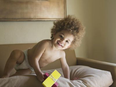 Mixed race boy playing with toy on sofa