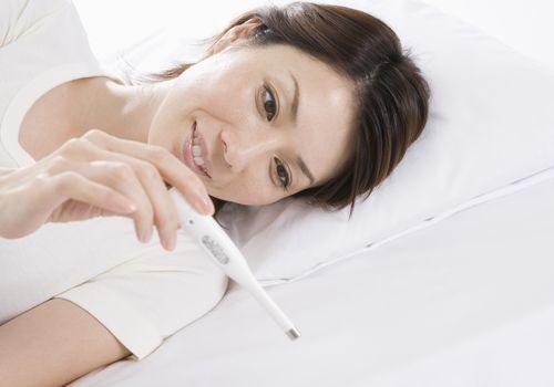Woman taking her body basal temperature