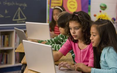 Students typing on laptop in classroom