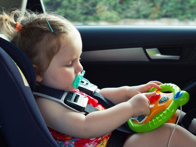Baby playing with toy in the car