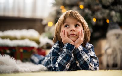 Little boy sitting in front of Christmas tree