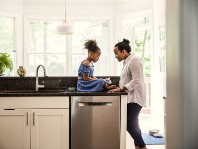 Mother and young daughter talking in kitchen