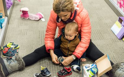 mother trying shoes on her baby in the aisle of a store