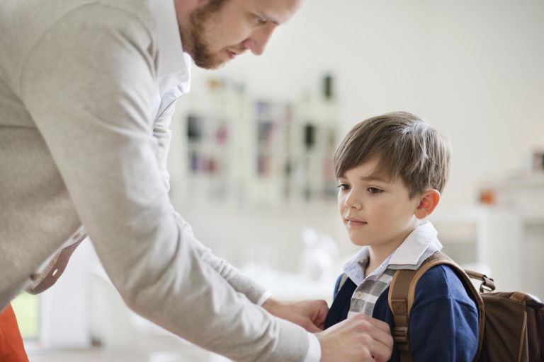 Man preparing his son for school