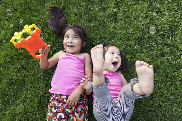 Two toddler girls lie on grass laughing as they play with bubble machine.