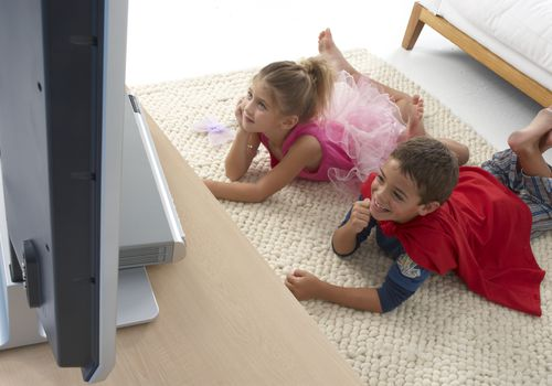 two children watching tv while wearing Halloween costumes